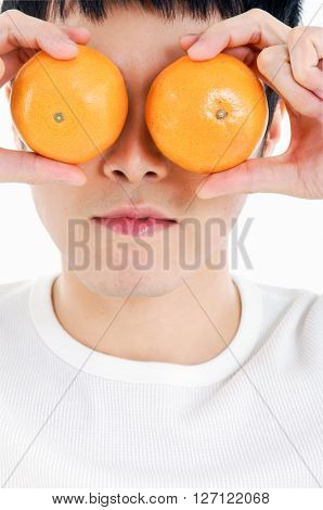 Young man is holding oranges in front of his eyes