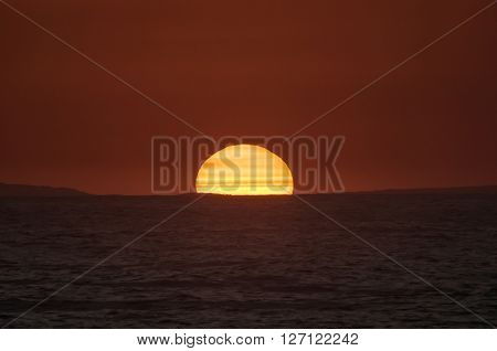 A fiery sunset over the Indian ocean on the Eastern Cape coast of South Africa. Sunspots are visible