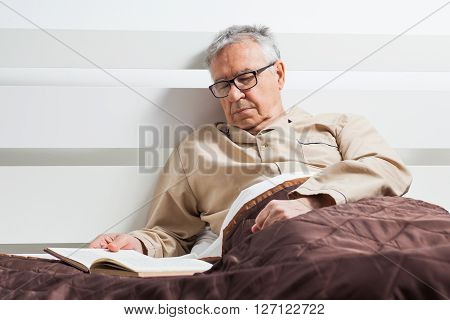 Senior man is lying in bed and he fell asleep while reading a book