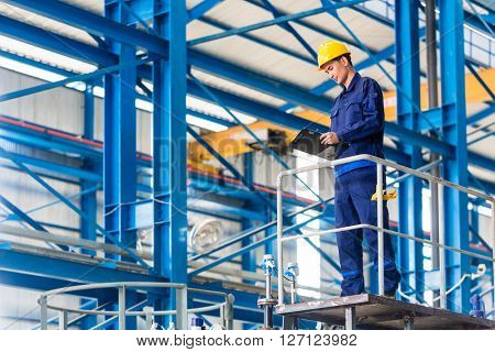 Worker in large metal workshop or factory checking work standing on large machine