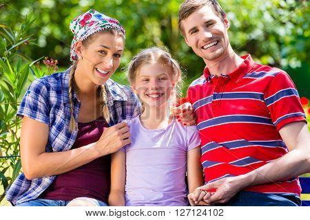 Family in garden sitting on bench