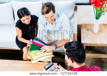 Mixed couple in furniture store with shop assistant discussing colors and material of items they are buying