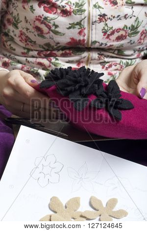 Woman working on a headdress. Sewing flower of cloth. Draw a sketch of the samples. Cuts flowers from wool fabric. Sewn on the beret. Handmade.