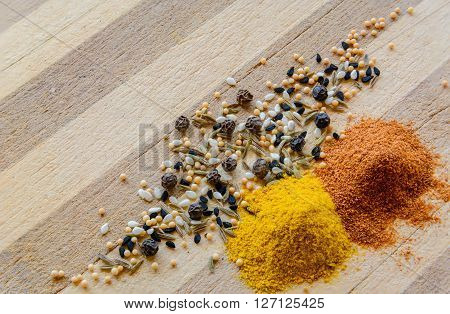 Spices sprinkled on a wooden board. Curcuma, black pepper, mustard seeds and black seeds.