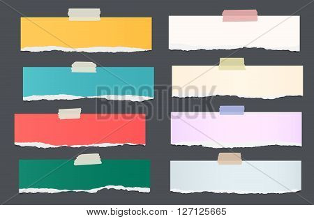 Set of ripped colorful note paper pieces are stuck on dark background.