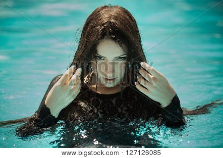 Portrait of the sexy woman relaxing in black fashion dress in pool. Creative photosessin of beautiful caucasian girl.