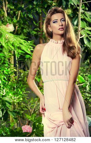 Elegant young woman in a long light dress posing in a blooming garden. Beauty, fashion.