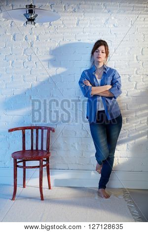 Casual young woman standing against wall arms crossed, looking down, thinking.