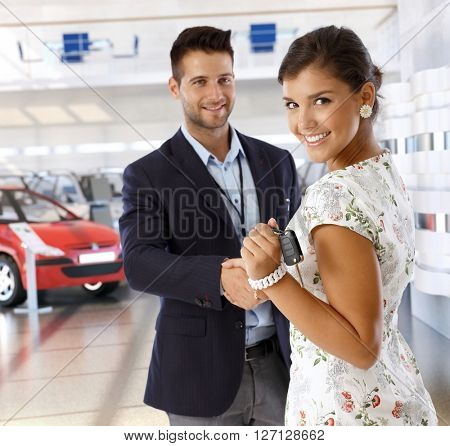 Attractive young caucasian casual businesswoman shaking hands with car dealer wearing suit at business dealership saloon, Looking at camera, smiling, standing, handing over keys.