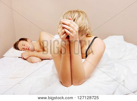 Young woman sitting on bed and crying, man sleeping