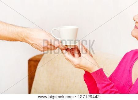 Man's hand giving cup of tea or coffee to senior woman