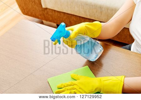 Young woman cleaning  table in yellow gloves