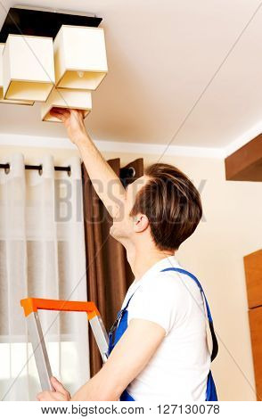 Young electrician working change a bulb at home