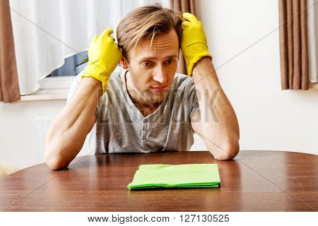 Tired man sitting behind the desk with cloth and gloves