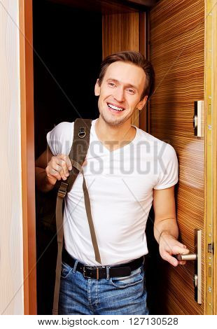 Young man returning home from work or trip