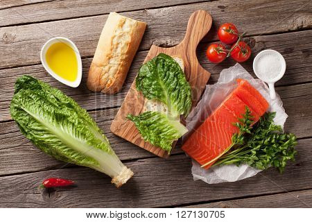 Sandwich with salmon and romaine salad cooking on wooden background. Top view