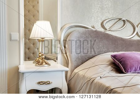 Little Table With A Lamp And A Bed With Pillows