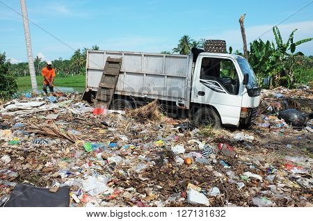 BALI INDONESIA - APRIL 10: A sanitation worker dumps household garbage into an illegal garbage dump contaminating rice fields and agricultural farmland on April 10 2016 in Ubud Bali Indonesia.