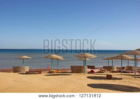 deserted beach, yellow sand, plenty of thatched beach umbrellas, sun beds, blue sea