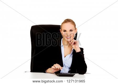 Smile business woman using calculator behind the desk