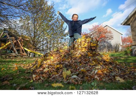 Boy jumping in a pile of autumn leaves