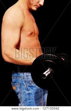 Side view of young muscular man weightlifting