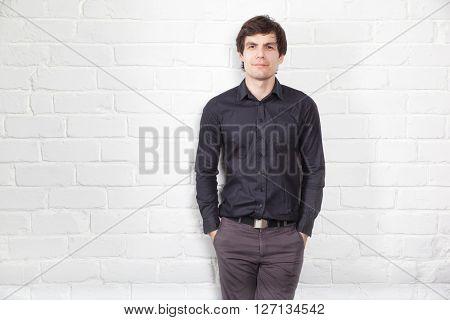 Young man and brick wall