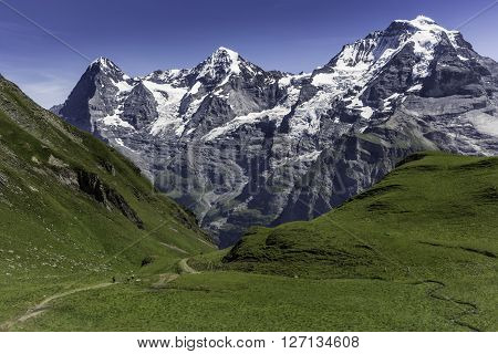 People hiking towards the famous three mountains in the Bernese Oberland in Switzerland