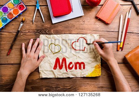 Mothers day composition. Hands of unrecognizable man painting hearts on piece of paper, school supplies. Studio shot on wooden background.