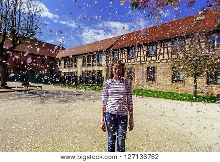 Teenage Girl Playing With Falling Petals On The Sun