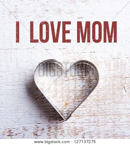 Mothers day composition. Heart shape cookie cutter. Studio shot on white wooden background.