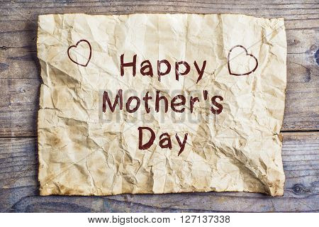 Happy mothers day sign on old rumpled sheet of paper. Studio shot on wooden background.