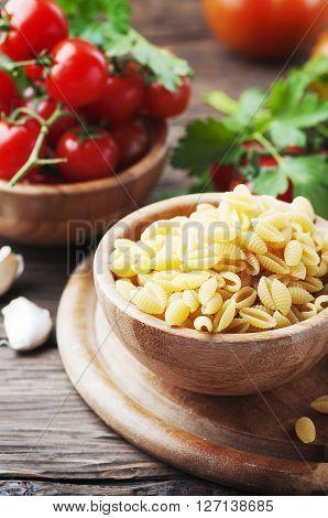 Sardinian uncooked pasta malloreddus with tomato selective focus