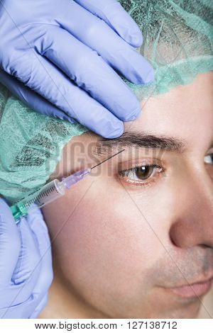 Doctor aesthetician makes hyaluronic acid rejuvenation beauty injections in the forehead under eyebrow of male patient in a green medical cap