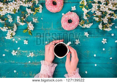The concept with morning coffee in a romantic style on the wooden background. Cherry blossoms, donuts, smartphone, coffee and hand in the frame.