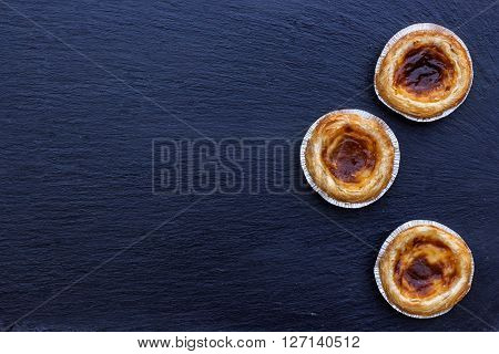 Egg tart on a grunge background, traditional portugueser dessert, pasteis de nata. Selective focus, flat lay, copy space