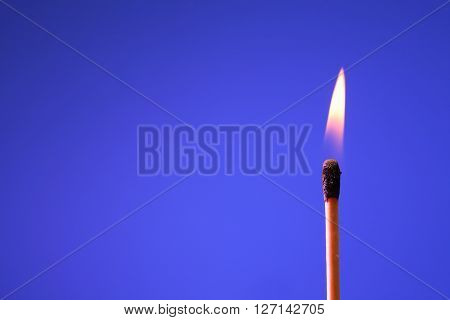 Lighting matchstick on blue background with free space for text