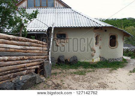 Ukrainian old house fence of logs granite stones
