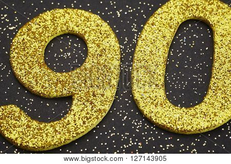 Number ninety golden color over a black background. Anniversary. Horizontal