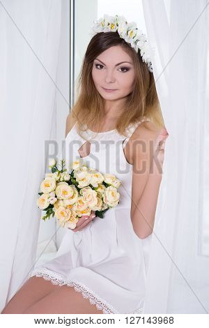Beautiful Woman In Short White Bridal Dress With Flowers Sitting On Window Sill