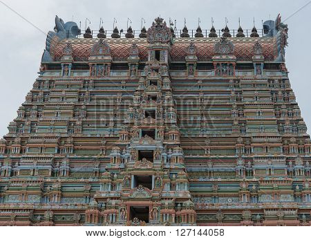 Trichy India - October 15 2013: Top half of the massive Rajagopuram of Ranganathar Temple. Eight levels and the long top the Vimanam. A wall of pastel colors pillars and statues.