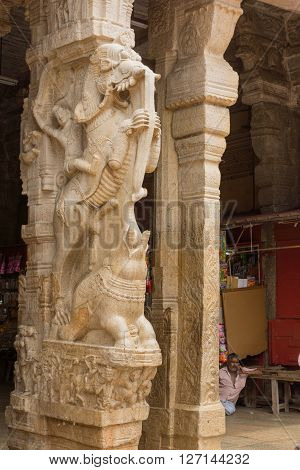 Trichy India - October 15 2013: Pillar forming statue of mythological beast the Yali or Vidala a combination of lion horse or elephant. Fighter rides animal. Small elephant and a sitting vendor in photo.