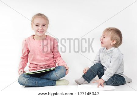 Cute little girl uses a tablet and boy laughing and playing with chalk and paper