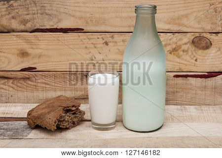 Rye bread with milk on wooden background