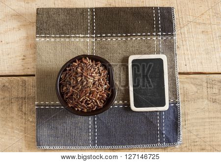 raw red rice in  bowl on a wooden table background