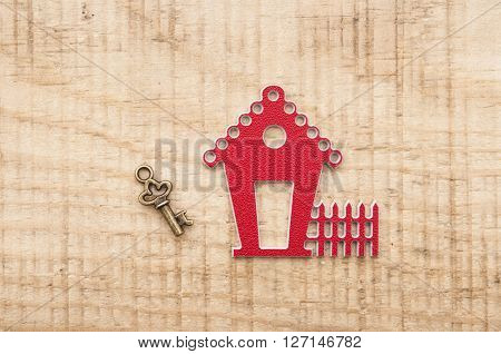 model house with vintage key on wooden background