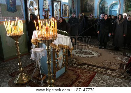 VOYUTYN UKRAINE - JANUARY 08: Uktainian parishioners of the Orthodox Church light up candles during Christmas service in Voyutyn on January 08 2009.