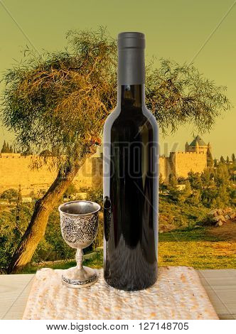 Conceptual collage with olive tree on holy hills of Jerusalem as background and unleavened bread, bottle of wine and silver cup as foreground for celebration of Jewish Passover