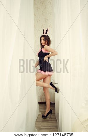 Lovely beautiful young woman posing in sensual lingerie and bunny ears. Studio shot.
