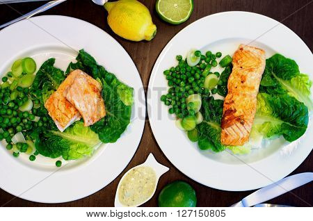 Delicious Roasted Salmon with Sweet Pea Leek and Salad Romano on White Plates with Lemon and Sauce closeup on Dark Wooden background. Selective Focus